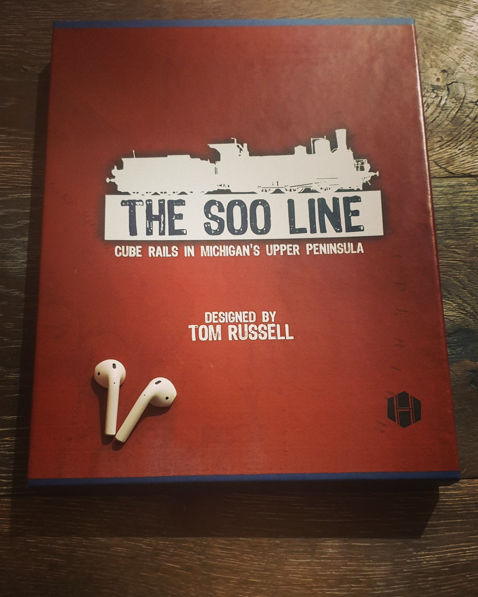 The Soo Line board game box and some airpods